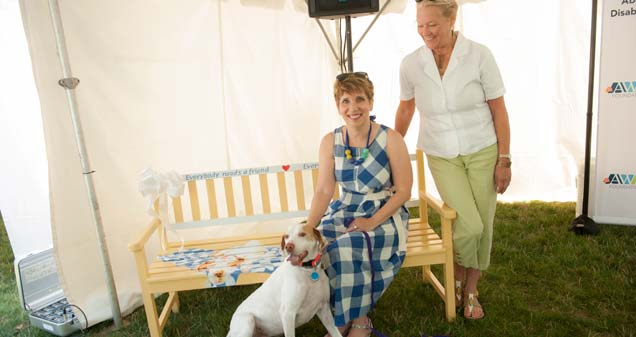 Patti Hays, AWS Foundation CEO and Buddy Bench honoree (seated), Vicki Junk-Wright, bench artist (standing) and  Bella (dog)